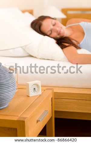 Alarm clock on bedside table woman sleeping in white bed