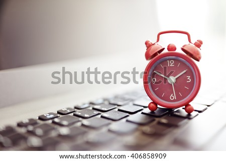 Alarm clock on laptop concept for business deadline, schedule and urgency - stock photo