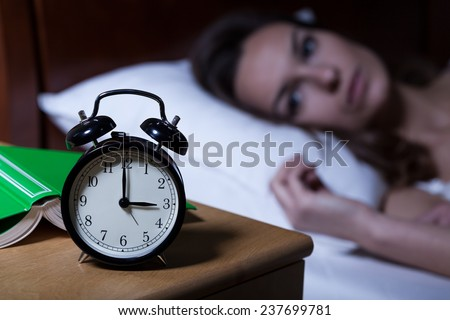 Alarm clock on night table showing 3 a.m. - stock photo