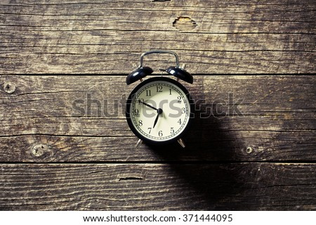 alarm clock on old wooden table - stock photo
