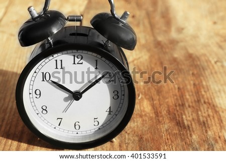 Alarm clock on old wooden table. - stock photo