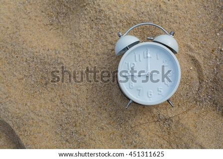 alarm clock on sand background - stock photo