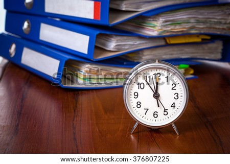 Alarm clock on table against pile of blue office folders