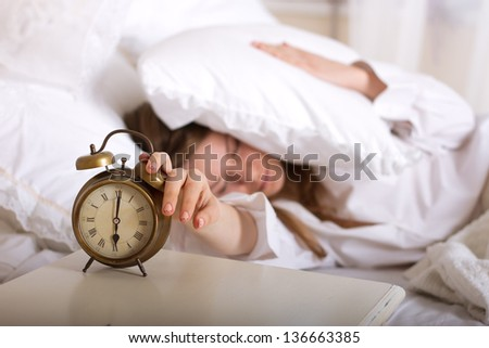 Alarm clock on table and woman sleeping in background - stock photo