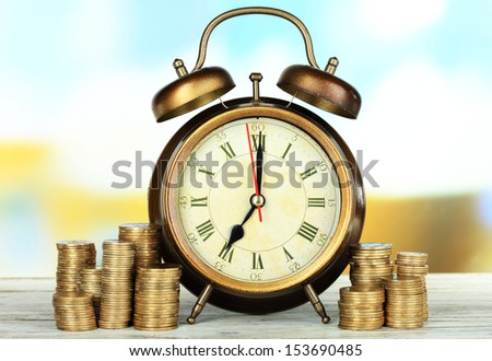 Alarm clock on table on bright background - stock photo