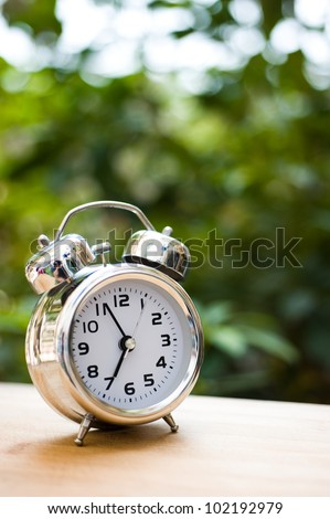 alarm clock on table with green background. - stock photo