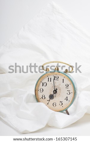 Alarm clock on the bed - stock photo