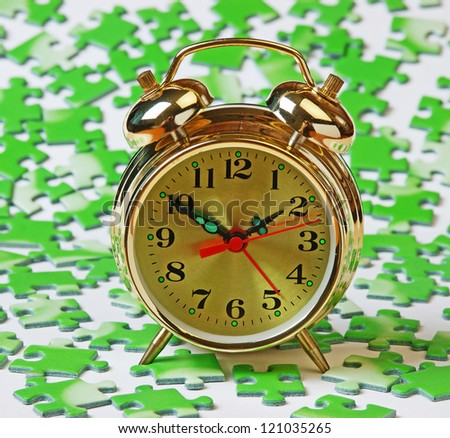 alarm clock on the green puzzle - stock photo