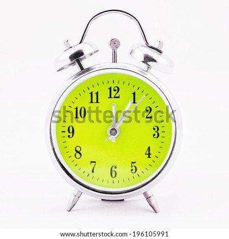 Alarm clock on white background. Showing time five minutes past twelve