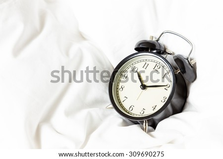 Alarm clock on white blanket