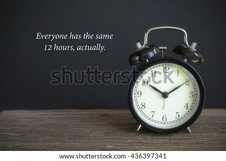 """Alarm clock on wood with a black background. Concept of time with word """"Every one has the same 12 hours"""" - stock photo"""