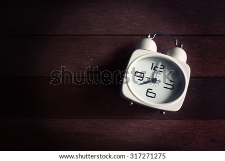 Alarm clock on wooden background. Vintage effect. - stock photo