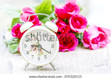 Alarm clock on wooden background with burred of pink roses as a background - stock photo