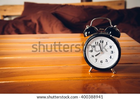 Alarm clock on wooden table in bedroom - stock photo