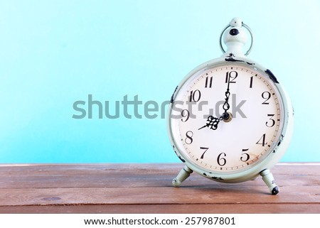 Alarm clock on wooden table on blue background - stock photo