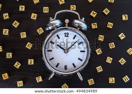 Alarm clock on wooden table with letters