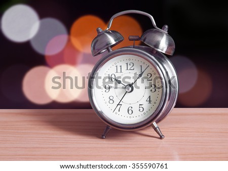 Alarm clock on wooden with abstract outdoor background