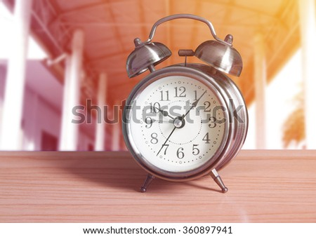 Alarm clock on wooden with outdoor background