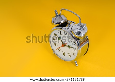 Alarm clock on yellow background
