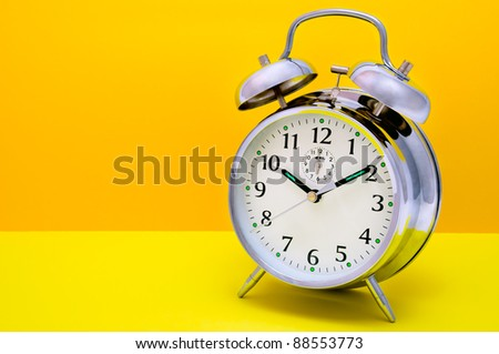Alarm Clock - Orange and yellow background - stock photo