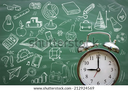 Alarm clock over blackboard with sketching school supplies - stock photo