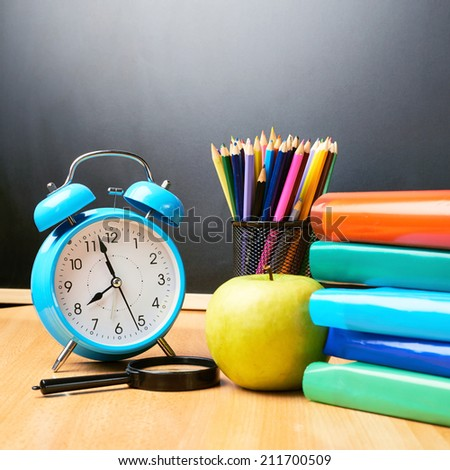 Alarm clock, pencils, apple, books against the blackboard as a back to school composition
