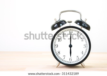 Alarm clock show 6 o`clock on old wood table.