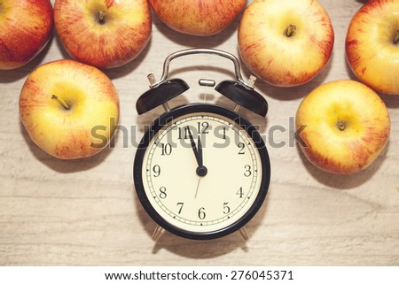 alarm clock showing almost twelve with red and yellow apples surrounding it. closeup - stock photo