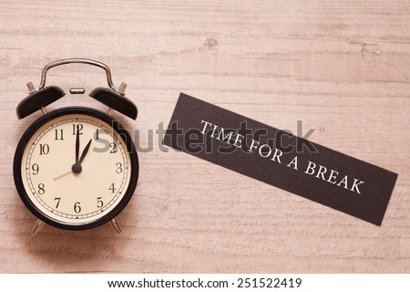 alarm clock showing one o'clock and indicating it is time for a break - stock photo