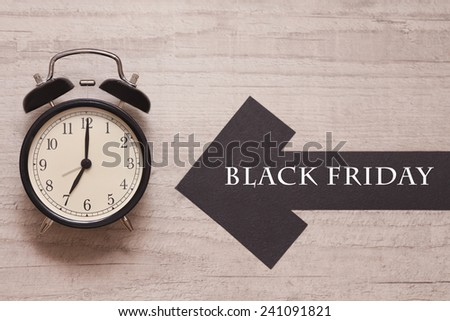 alarm clock showing seven with arrow sign indicating black friday - stock photo