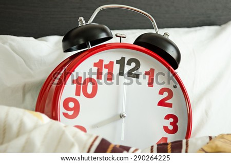 alarm clock sleeping in bed - stock photo