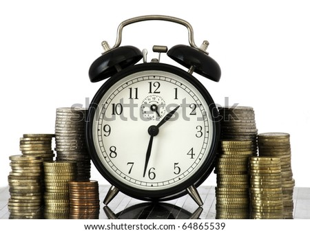 Alarm clock standing with coins on metal plate - stock photo