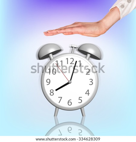 Alarm clock stands on the blue background and womans hand atop - stock photo