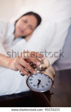 Alarm clock successfully woke up young woman - stock photo