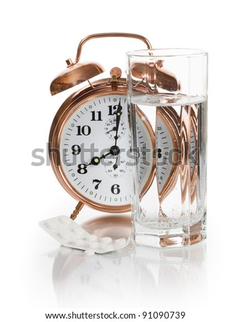 Alarm clock, tablets and glass of water on white background - stock photo