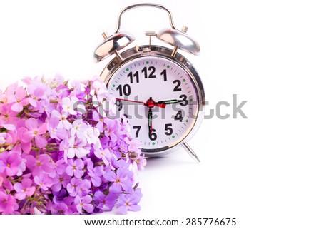 alarm clock violet flowers night morning selective soft focus - stock photo