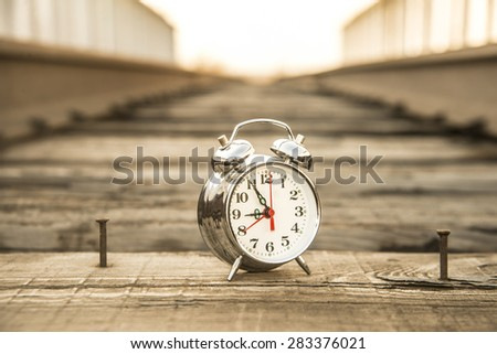 alarm clock  Watch outdoor alone against wooden sleeper between metal rusty rails and fence of bridge against sky background Idea symbol of tourism travel Too late train left - stock photo