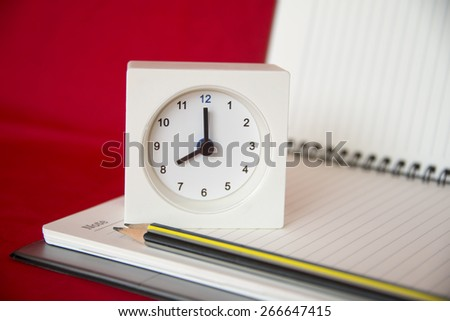 alarm clock with and notebook - stock photo
