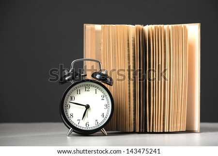 alarm clock with book on black background - stock photo
