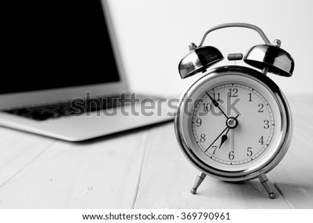 Alarm clock with computer laptop on desk in black and white - stock photo