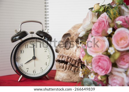 alarm clock with cranium, flowers and notebook - stock photo