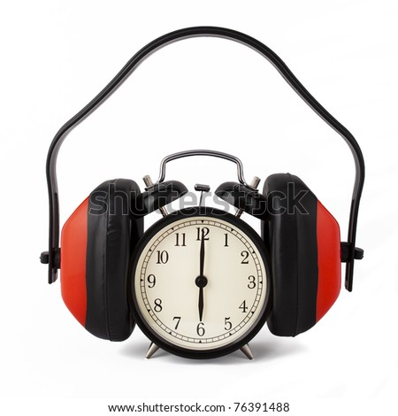 Alarm clock with ear defenders on. Conceptual idea to not want to hear the alarm clock when it goes off. White background.