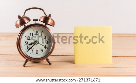 Alarm clock with empty sticky note - stock photo