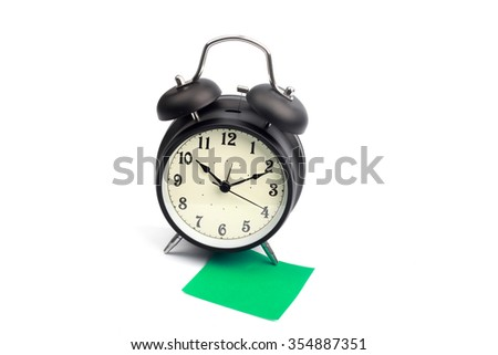 Alarm clock with green sticky paper - stock photo