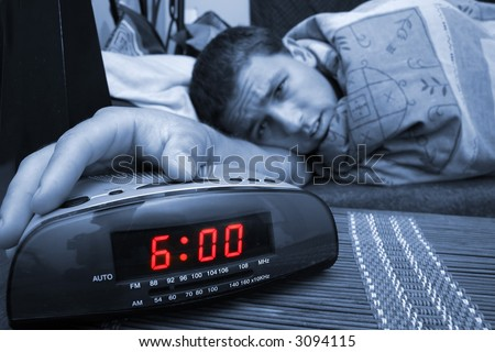 Alarm clock with male model in bed in background. Shallow depth of field