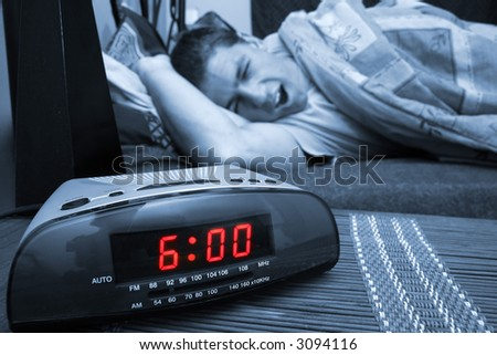 Alarm clock with male model in bed in background. Shallow depth of field - stock photo