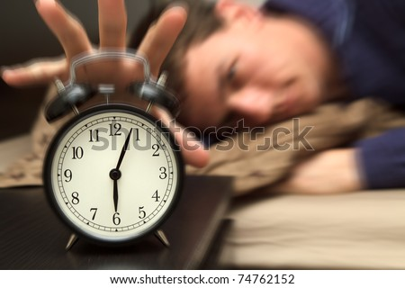 Alarm clock with male model in bed in background. Shallow depth of field, motion blur to show critical realization - stock photo