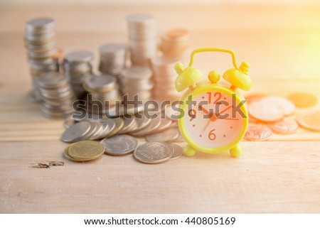 alarm Clock with money on wooden table business concept - stock photo