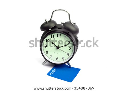 Alarm clock with note blue sticky paper - stock photo