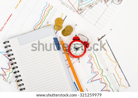 Alarm clock with notebook and pencil on business documents background